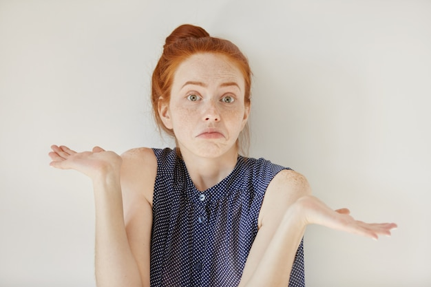 Verbaasde en onwetende jonge roodharige vrouw met uitgestrekte armen, schouderophalend zeggend: who cares, so what, ik weet het niet. negatieve menselijke emoties, gezichtsuitdrukkingen, levensperceptie en houding Gratis Foto