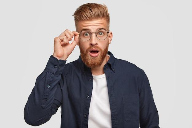 Verbaasde hipster-man met geschokte uitdrukking, hoort iets ongelooflijks, houdt de hand op de rand van een ronde bril, opent de mond van verrassing, gekleed in een stijlvol shirt, geïsoleerd op een witte muur Gratis Foto