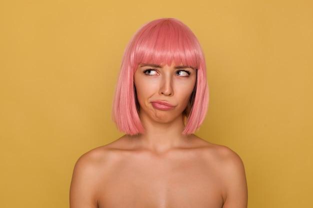 Verbaasde jonge aantrekkelijke roze harige vrouw met natuurlijke make-up die haar mond verdraait terwijl ze verward naar boven kijkt, poseren over mosterdmuur met blote schouders Gratis Foto
