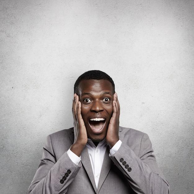 Verbaasde jonge afrikaanse zakenman gekleed in formele kleding, kijkt opgewonden en geschokt, hand in hand op de wangen, schreeuwend met wijd open mond, verbaasd over winstgevend zakelijk aanbod of grote verkoop Gratis Foto