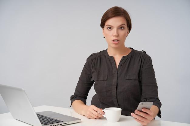 Verbaasde jonge bruinogige kortharige brunette vrouw die verwarrend wenkbrauw opheft, mobiele telefoon in haar hand houdt terwijl ze poseren op wit Gratis Foto