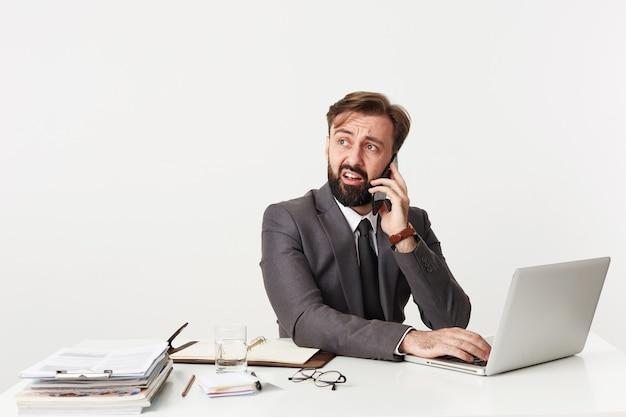 Verbaasde jonge brunette man met baard opzij kijken met verward gezicht en zijn voorhoofd rimpelen, bellen met smartphone zittend aan tafel met handen op toetsenbord van zijn laptop Gratis Foto