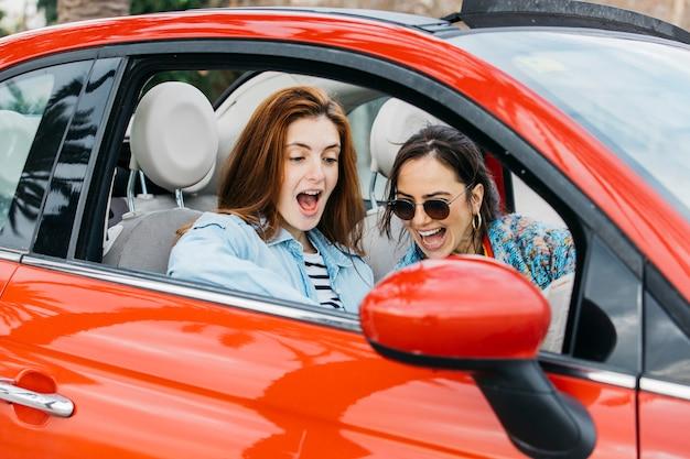 Verbaasde jonge dame en vrolijke vrouwenzitting in auto Gratis Foto