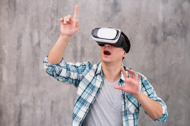 Verbaasde jonge man in vr-headset Gratis Foto