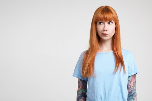 Verbaasde jonge roodharige vrouw met tatoeages die haar mond draaien terwijl ze peinzend opzij kijkt, haar handen langs het lichaam houdt terwijl ze poseren op witte achtergrond Gratis Foto