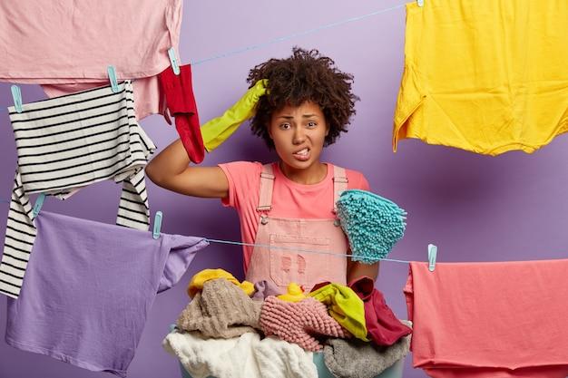 Verbaasde jonge vrouw met een afro poseren met wasgoed in overall Gratis Foto