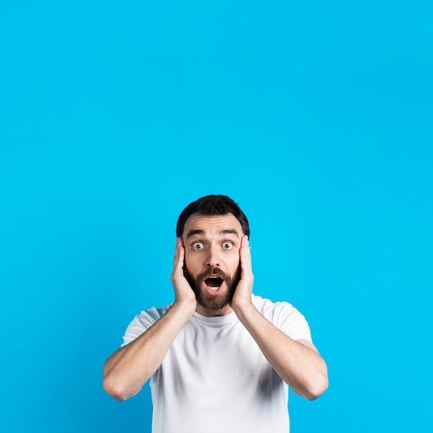 Verbaasde man die zijn hoofd met handen houdt Gratis Foto