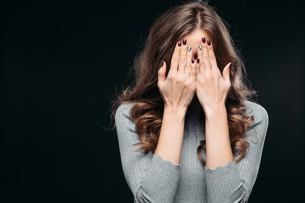 Verbaasde mooie vrouw die gezicht behandelt met hand Premium Foto