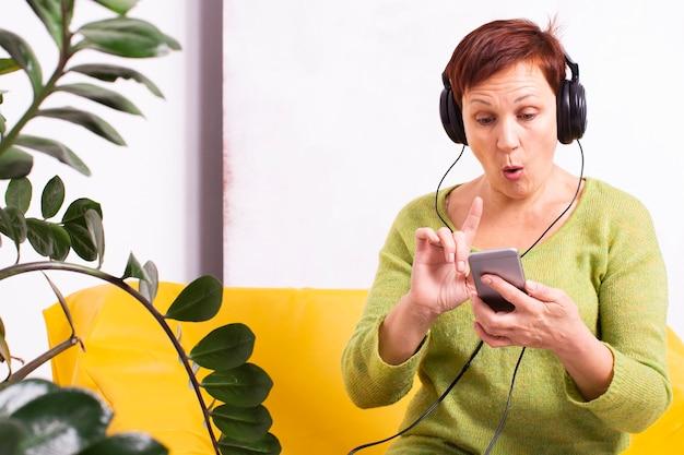 Verbaasde senior vrouw luisteren muziek Gratis Foto