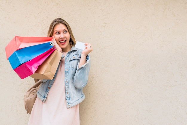 Verbaasde vrouw die zich met het winkelen zakken en creditcard bij muur bevindt Gratis Foto
