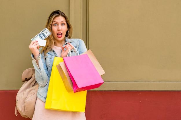 Verbaasde vrouw die zich met het winkelen zakken en geld bevindt Gratis Foto
