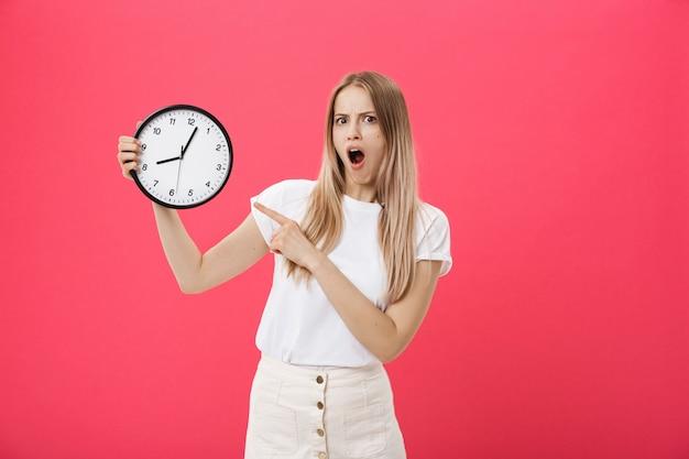 Verbaasde vrouw met klok. de verraste vrouw in witte t-shirt houdt zwarte klok. retro stijl. tijdsbesparing concept. zomer uitverkoop. korting. geïsoleerd op roze achtergrond. Premium Foto