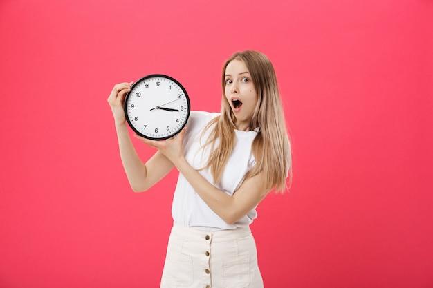 Verbaasde vrouw met klok. de verraste vrouw in witte t-shirt houdt zwarte klok Premium Foto