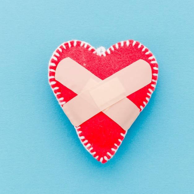 Verband over de witte vorm van het steek rode hart op blauwe achtergrond Gratis Foto