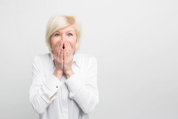 Verbazingwekkend mooie en prachtige oude vrouw houdt haar hand op de mond en laat zien dat ze erg verrast is. Premium Foto