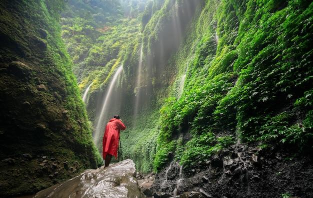 Verbazingwekkende avontuur jonge man fotograaf in rode regenjas staande op steen en waterval Premium Foto