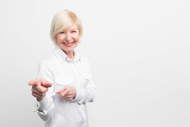 Verbazingwekkende en vrouwelijke oude vrouw draagt een witte blouse en wijst op iets. ze ziet er zelfverzekerd en gelukkig uit. Premium Foto