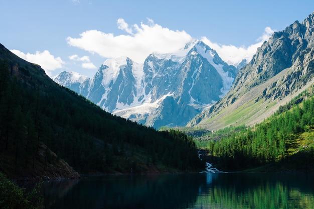 Verbazingwekkende gletsjer onder de blauwe hemel. bos weerspiegeld schoon water van bergmeer. Premium Foto