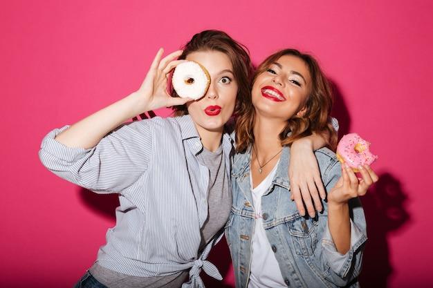 Verbazingwekkende twee vrouwelijke vrienden die donuts eten Gratis Foto