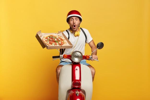 Verbijsterde knappe mannelijke bestuurder op autoped met rode helm die pizza levert Gratis Foto