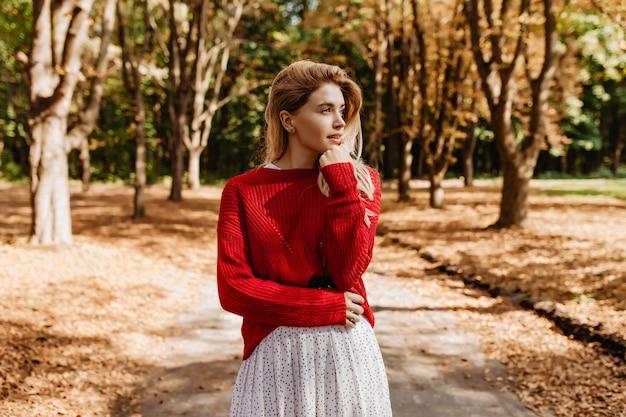Verbluffende blonde in stijlvolle kleding die ver in het herfstbos kijkt. mooie meid geniet buiten van mooi weer. Gratis Foto