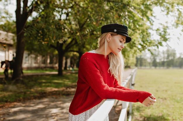Verbluffende blondine met een elegante stijl die zich goed voelt buiten. charmant meisje poseren in de buurt van oud gebouw in het park. Gratis Foto