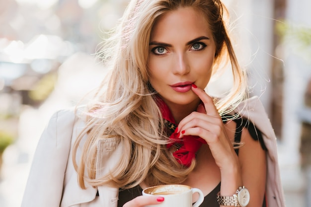 Verbluffende gebruinde dame poseren speels aanraken van lippen met vinger. vrij blond meisje kopje thee houden en kijken met belangstelling Gratis Foto