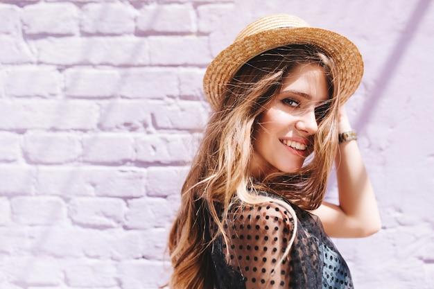 Verbluffende langharige dame met grote ogen poseren buiten wandelen langs bakstenen muur Gratis Foto