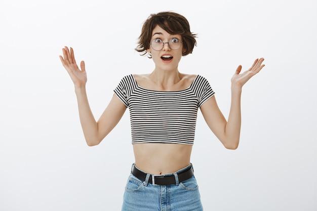 Verbluffende vrouw die verrast en gelukkig handen opheft Gratis Foto
