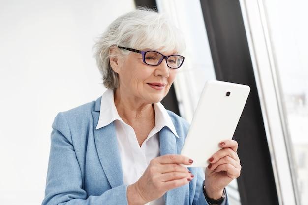 Verbonden blijven. moderne slimme bejaarde vrouw met grijs haar poseren geïsoleerd in glazen en formele kleding, elektronisch boek lezen of online winkelen met behulp van digitale tablet, blij blij kijken Gratis Foto