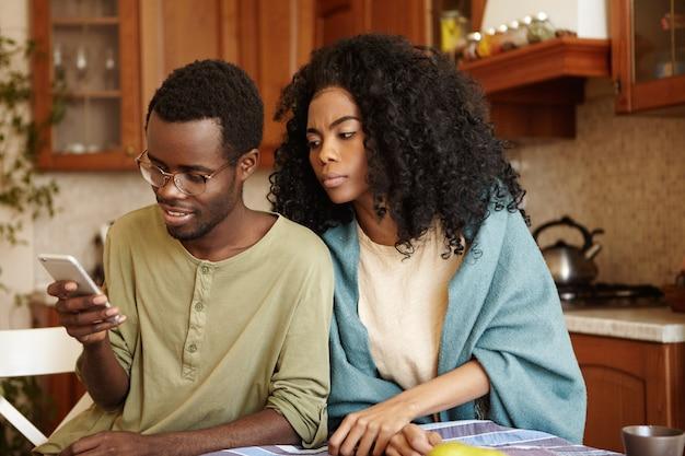 Verdachte zwarte vrouw probeert bericht te lezen dat haar gelukkige echtgenoot naar iemand op de mobiele telefoon stuurt omdat ze verraad vermoedt, hem niet vertrouwend. jaloezie, ontrouw en wantrouwen Gratis Foto