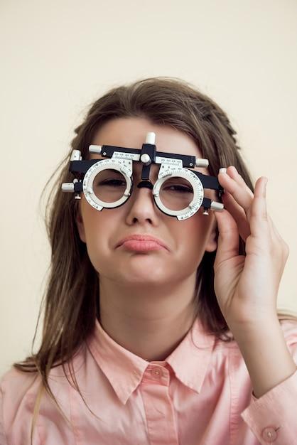 Verdrietig meisje heeft oogproblemen. portret van boos sombere europese vrouw in oogarts kantoor, visie testen zittend en dragen phoropter, betreurend dat ze zicht in de buurt van computer bedorven Gratis Foto