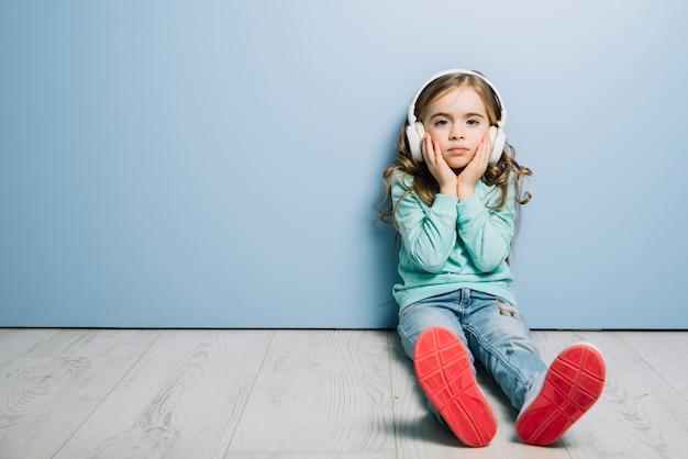 Verdrietig meisje, zittend op de vloer tegen blauwe muur luisteren muziek op de koptelefoon Gratis Foto