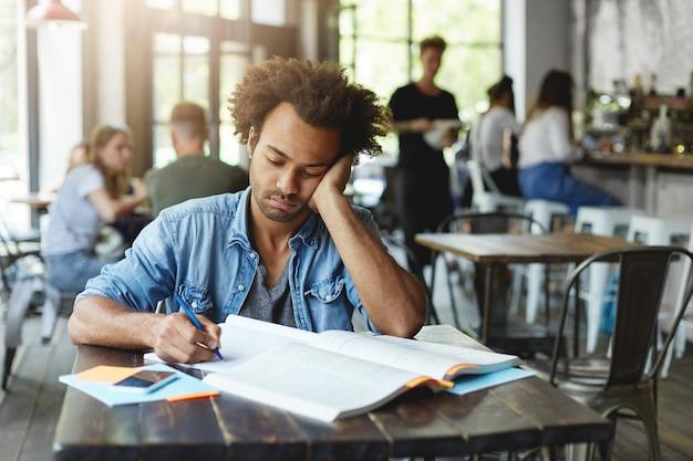 Verdrietige, ongelukkige, donkere, bebaarde student die zich gefrustreerd voelt terwijl hij zich voorbereidt op lessen op de universiteit, met pen in zijn schrift opschrijft, op zijn elleboog leunt en met een verstoorde uitdrukking naar aantekeningen kijkt Gratis Foto