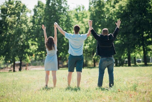 Verenigde mensen die en handen opstaan houden Gratis Foto