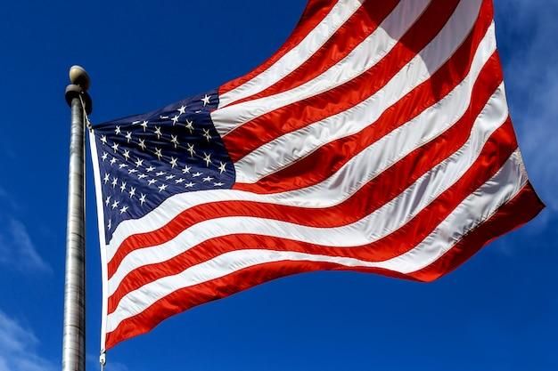 Verenigde staten van amerika. windgeblazen vlag de verenigde staten van amerika over hemelachtergrond. Premium Foto