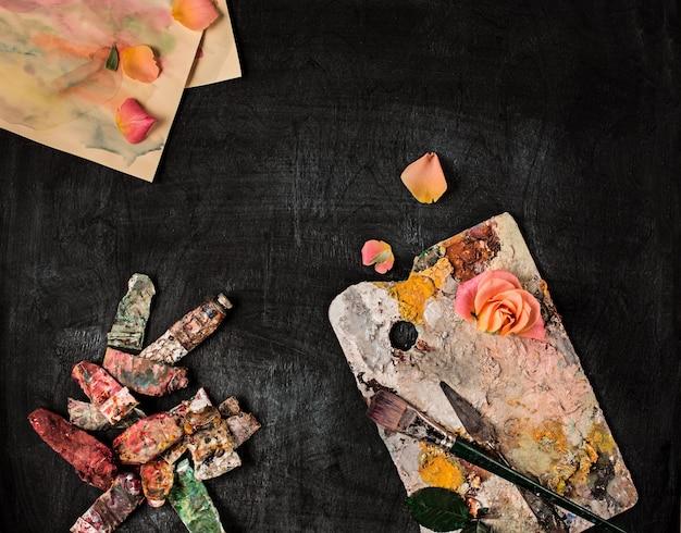 Verfborstels en buizen van olieverf op houten muur Gratis Foto