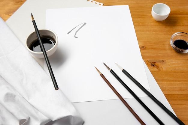 Verfborstels en zwarte inkt op papier Gratis Foto