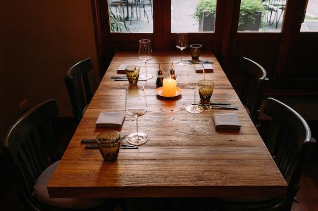 Verfijnde houten tafel met bestek, wijnglazen, servetten, luiers en brandende kaars op tafel. Premium Foto