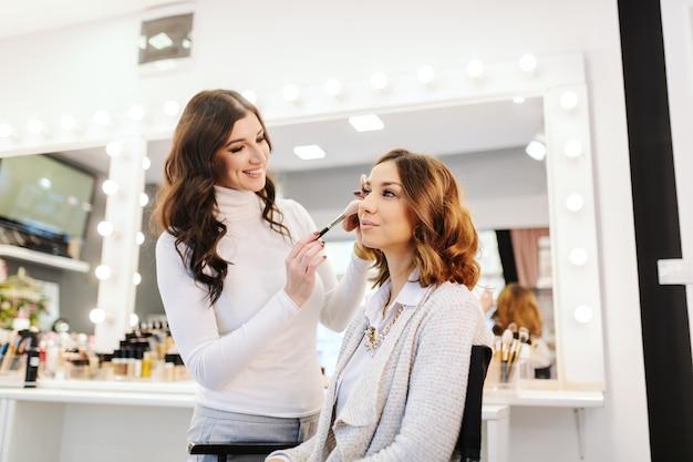 Verfijnde mooie kaukasische brunette zitten in de schoonheidssalon terwijl make-up artiest blozen zetten op de wangen van de vrouw. Premium Foto