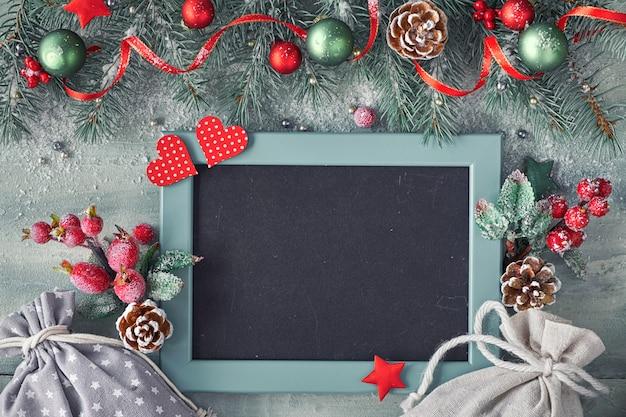 Verfraaide donkere achtergrond met rode en groene decoratie en spartakjes, tekst Premium Foto