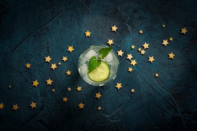 Verfrissend drankje met ijs, komkommer en munt op een donkerblauwe achtergrond met sterren. concept nachtclub, nachtleven, feest, dorst. plat lag, bovenaanzicht Premium Foto