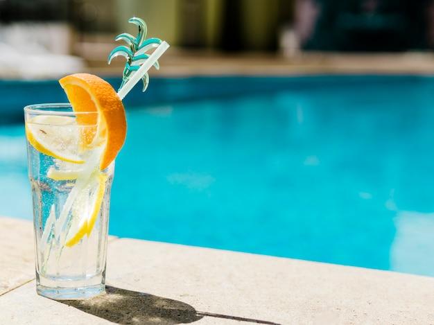 Verfrissende cocktail met sinaasappel en citroen bij zwembad Premium Foto