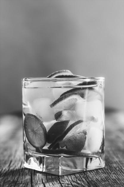 Verfrissende drank met groene citroen en ijs dicht omhoog, zwart en wit Premium Foto