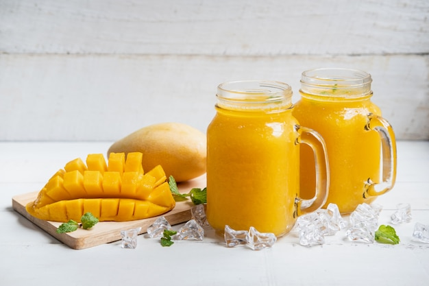 Verfrissende mango smoothies in glas met rijpe mango op witte houten tafel Premium Foto