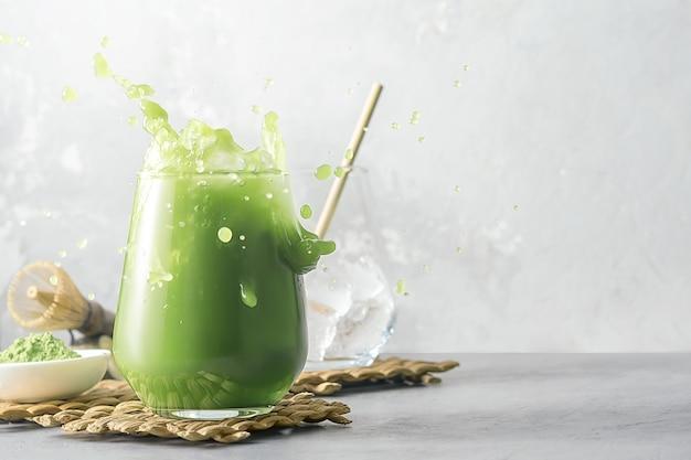 Verfrissende matcha-thee met ijs en spatten op een grijze achtergrond met exemplaarruimte. Premium Foto