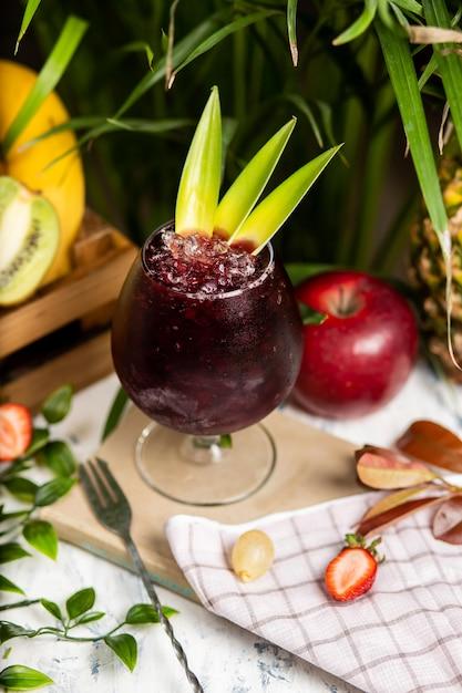 Verfrissende zomeralcoholische cocktailmargarita met verpletterd ijs en citrusvruchten binnen glas met aardbeien en appel op keukenlijst Gratis Foto