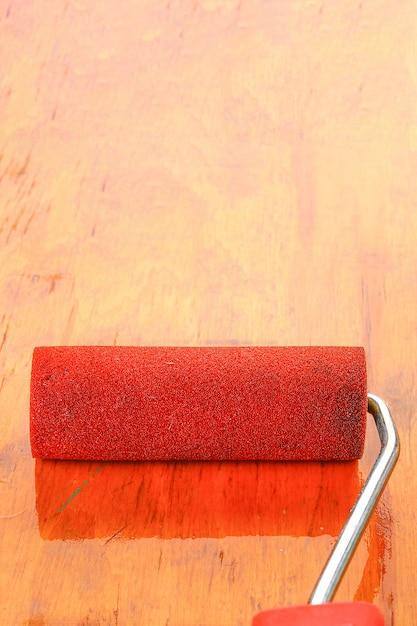 Verfrollerborstel in verf op triplexoppervlak. Premium Foto