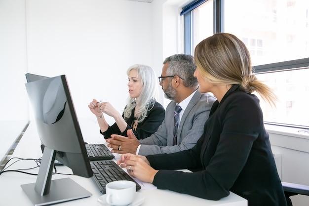 Vergadering van bedrijfsmanagers. team van professionals zitten op de werkplek met monitoren samen en project bespreken. zijaanzicht. zakelijke bijeenkomst concept Gratis Foto