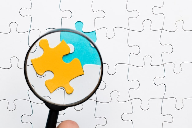 Vergrootglas die zich op geel raadselstuk over de witte achtergrond van het raadselstuk concentreren Gratis Foto